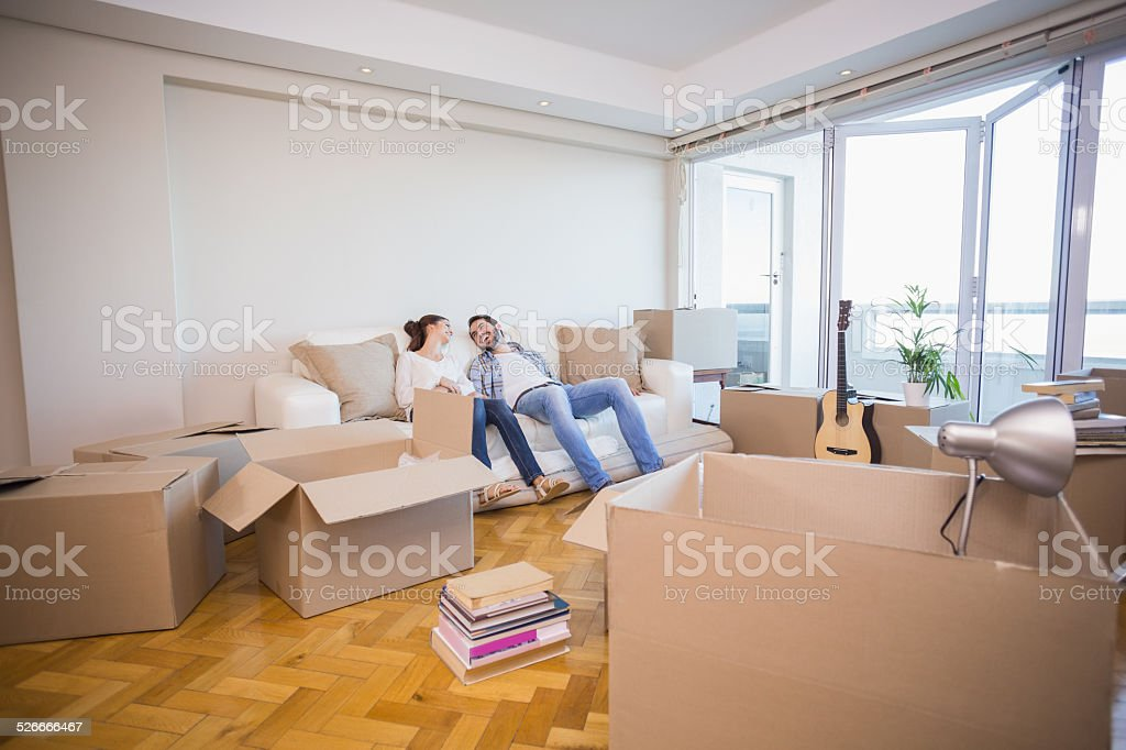 Cute couple taking a break from unpacking stock photo