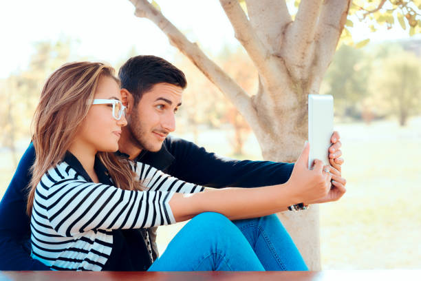 Cute Couple Using PC Tablet Outdoors in Nature stock photo