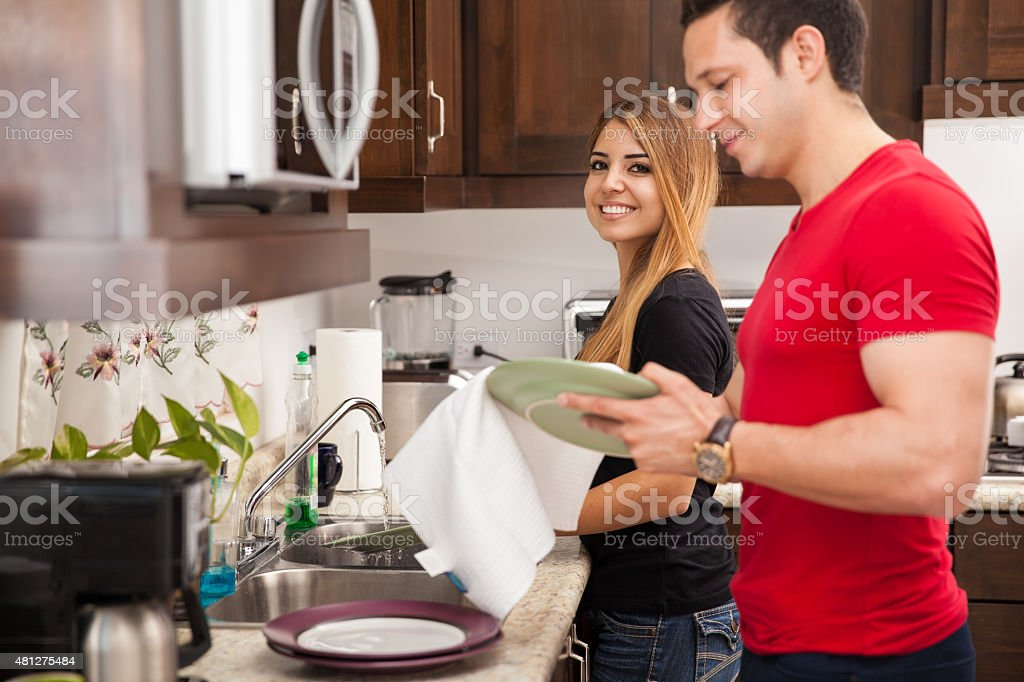 Cute couple washing the dishes stock photo
