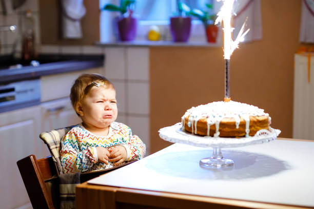 Cute crying little baby girl celebrating first birthday. Child scared and afraid of firework on baked cake, indoor. Toddler chil not happy Cute crying little baby girl celebrating first birthday. Child scared and afraid of firework on baked cake, indoor. Toddler chil not happy. birthday wishes for daughter stock pictures, royalty-free photos & images