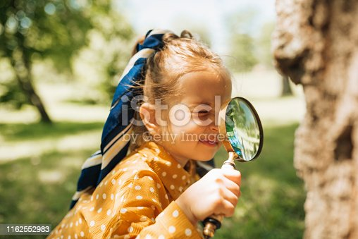 istock Cute curious kid with magnifying glass exploring the nature and insects outdoor. Adorable little girl playing in forest with magnifying glass. Child looking through magnifier on a sunny day in park 1162552983