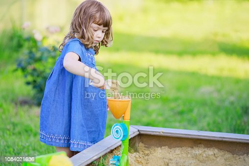 Cute curly little girl playing in the sandbox outdoors, warm summer day.