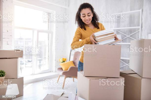 Cute curlyhaired girl packing books before moving out picture id962089004?b=1&k=6&m=962089004&s=612x612&h=svj emvqk5ncyudkwlp tbd6hzafrkticdeumkkhojk=