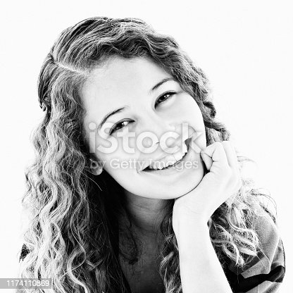A cute curly-haired teenager leans on her fist, head tilted, and smiles. Black and white.