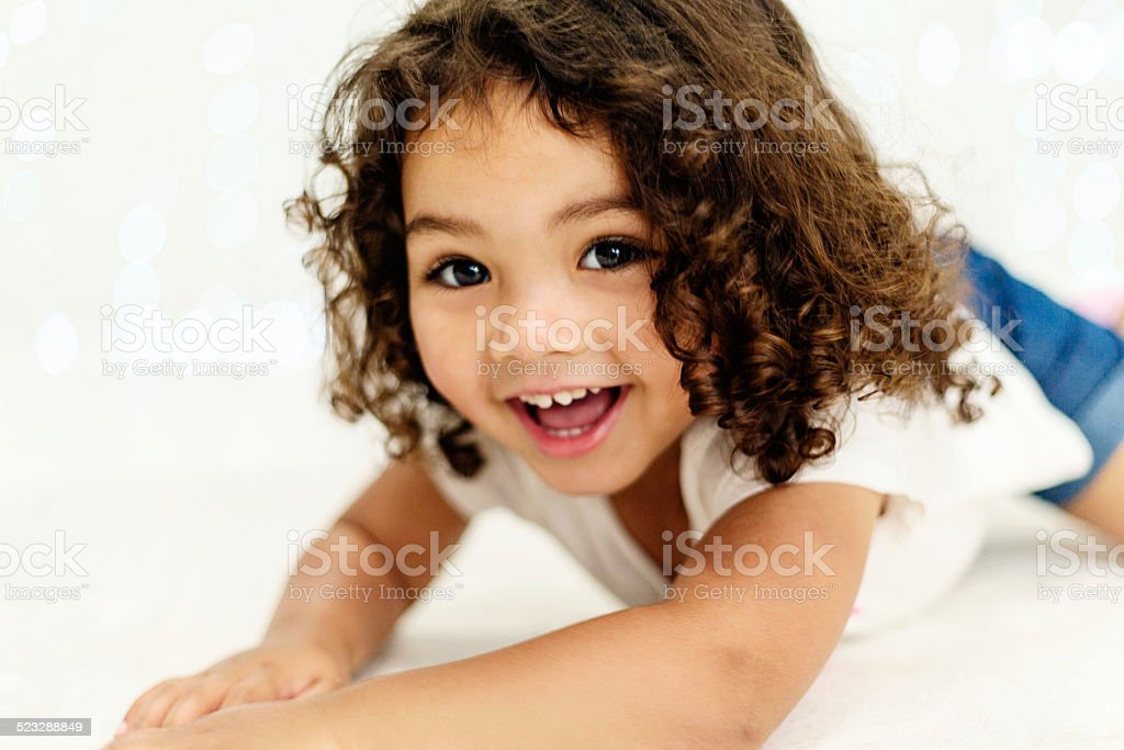 Cute, curly-haired toddler girl gives an adorable cheeky smile stock photo