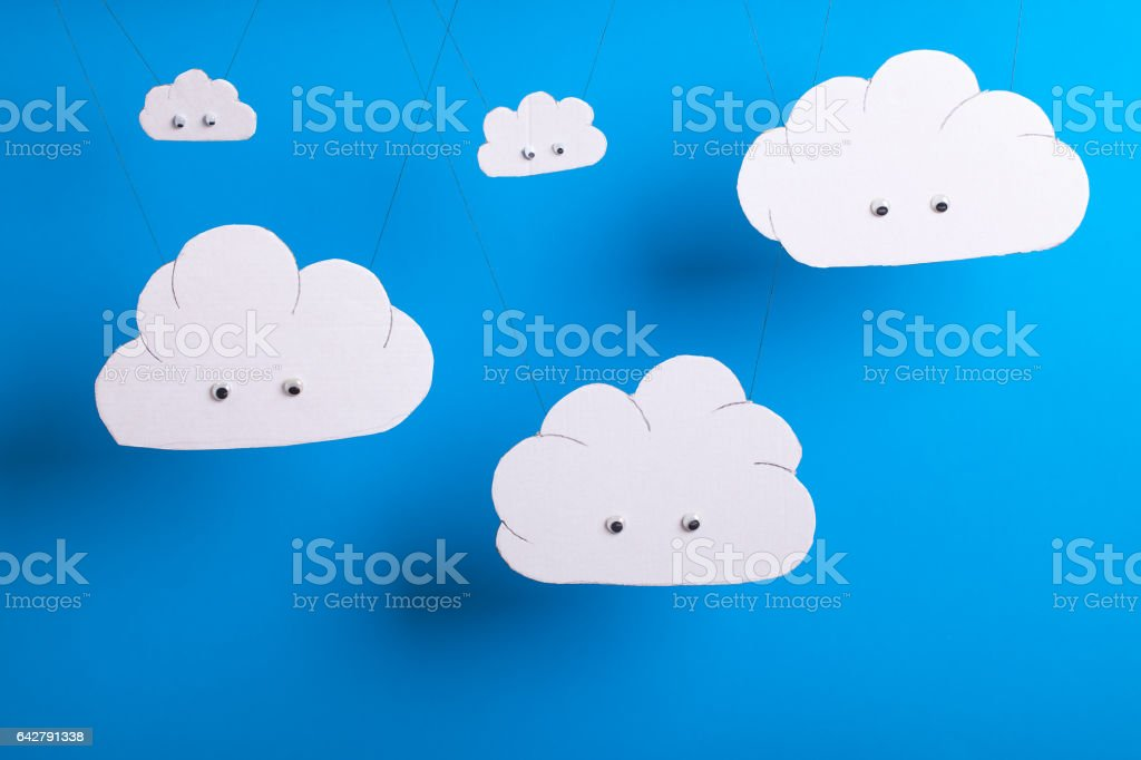Cute cutout clouds hanging with sky blue background stock photo