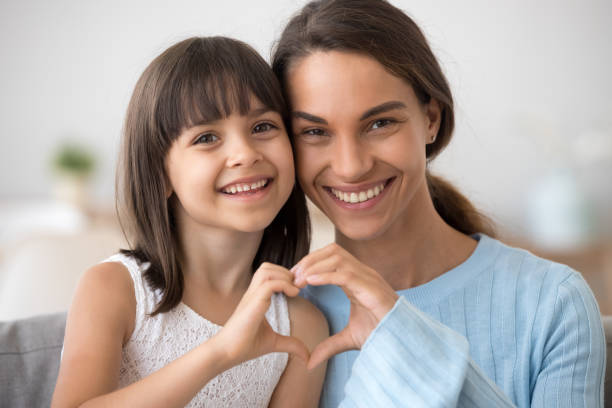 Cute daughter and happy mother join hands in heart shape Cute little daughter and happy mother join hands in shape of heart as concept of mom and child love care support, smiling mum and her kid girl looking at camera posing together for headshot portrait healthy heart stock pictures, royalty-free photos & images