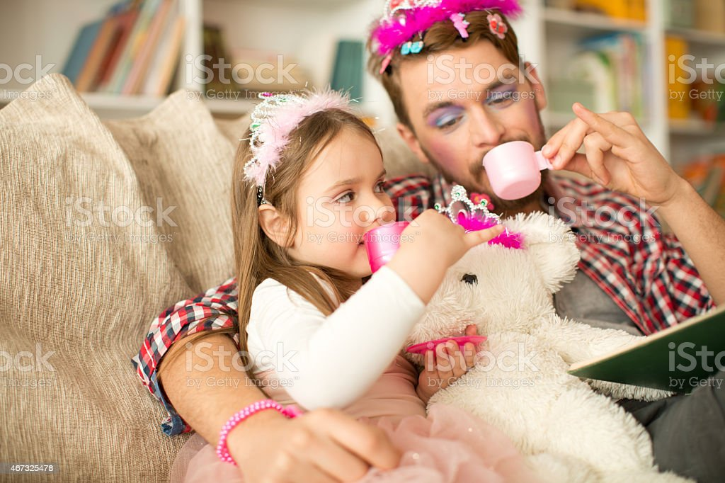 Cute daughter and her father having princess time. stock photo