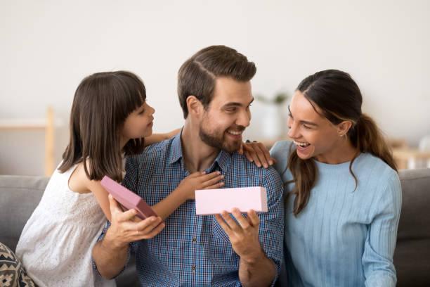 niedliche tochter und frau gratulieren glücklichen vater geschenk-box öffnen - geburtstagsgeschenk für papa stock-fotos und bilder