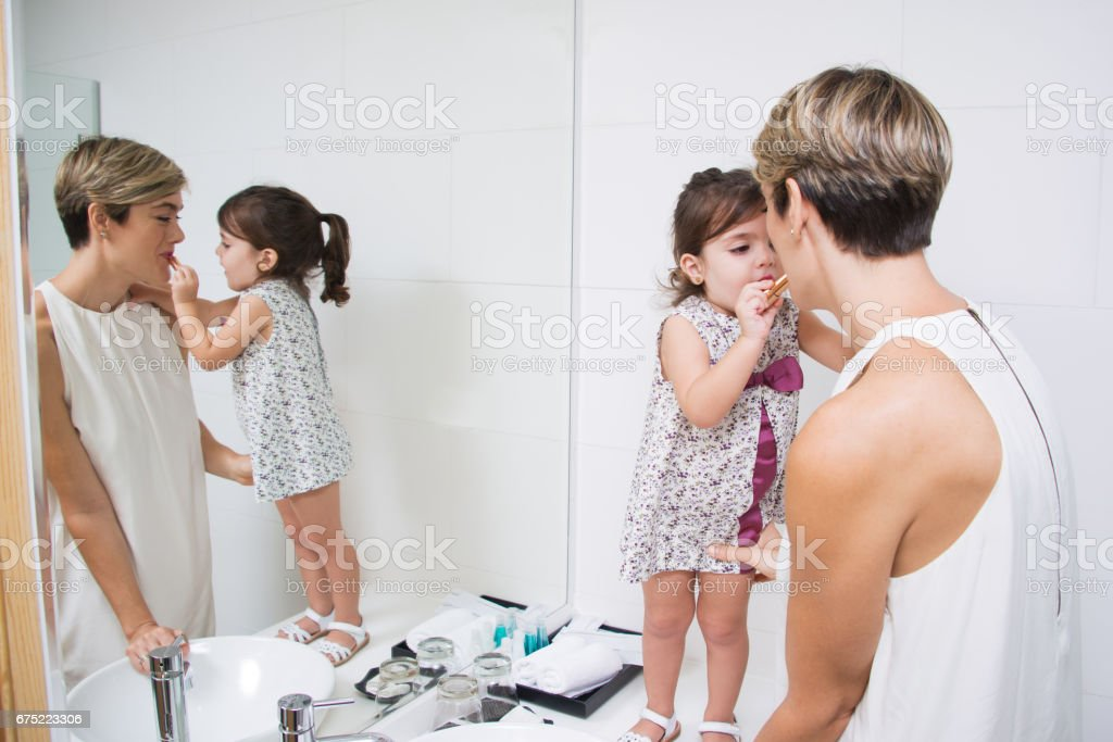 Cute daughter applying lipstick on mothers lips royalty-free stock photo