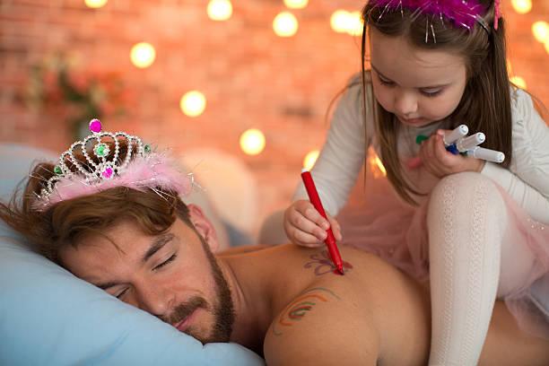 süße tochter malen auf ihr schlafen vaters rücken. - papa humor stock-fotos und bilder