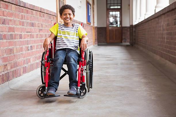 linda discapacitados alumno sonriendo a la cámara en hall - wheelchair fotografías e imágenes de stock