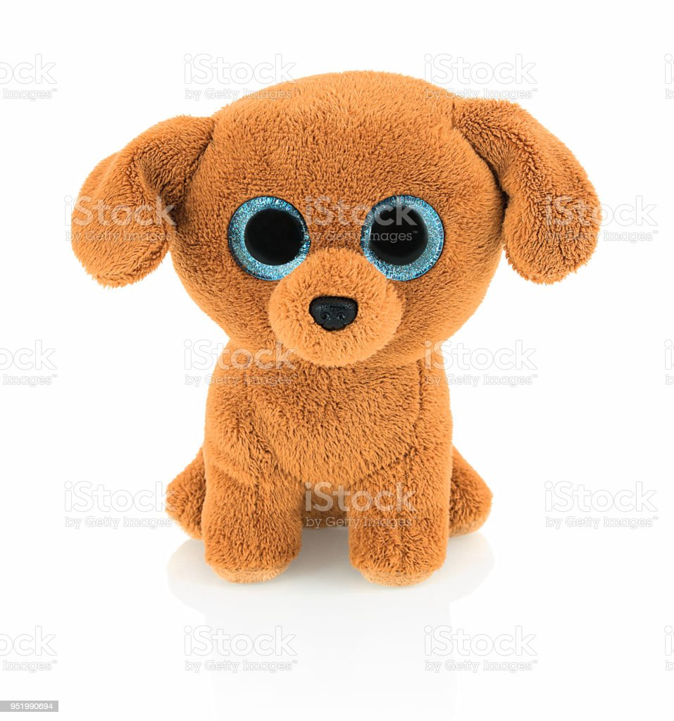 Cute dog doll with blue eyes isolated on white background with shadow reflection. Playful bright brown dog toy sitting on white underlay. stock photo