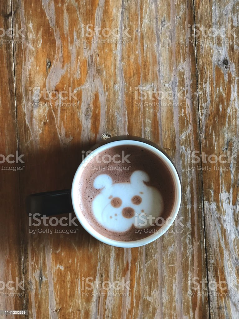 Cute dog face latte art coffee in white cup on wooden table , love...