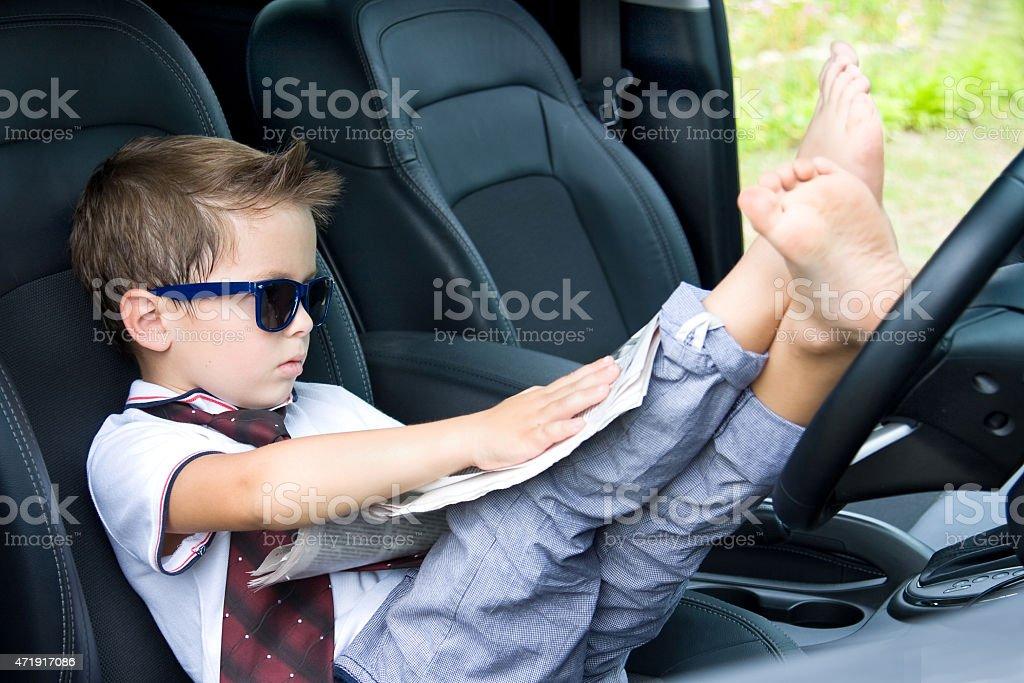 Cute driver reads newspaper in car stock photo