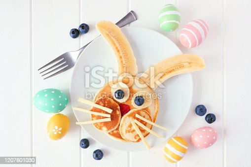 istock Cute Easter Bunny pancakes on a white plate, top view over white wood 1207601030