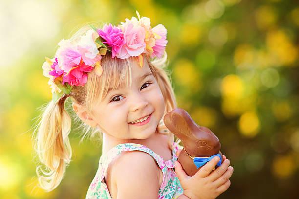 süße ostern-mädchen mit schokolade bunny - kinderschokolade stock-fotos und bilder