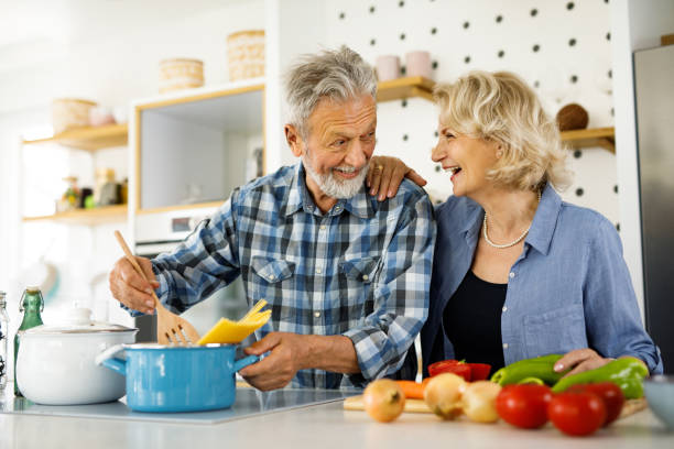 Cute elderly couple preparing family dinner in the kitchen stock photo