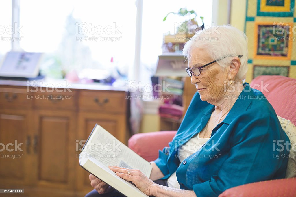 Cute elderly woman reading a book in longterm care facility stock photo