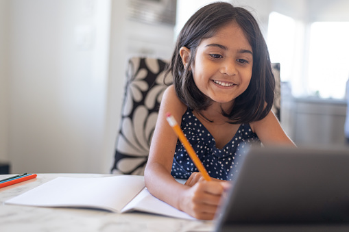 An adorable elementary age girl of Indian descent smiles while doing school assignment online as she studies at home during Covid-19 pandemic. The girl is using a tablet computer to attend a class using a video call. Distance learning and homeschooling concepts.