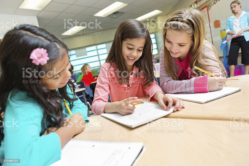 Cute elementary age girls studying together in public school classroom royalty-free stock photo
