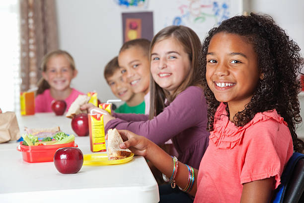 Mignon élémentaire des enfants ayant le déjeuner à l'école - Photo
