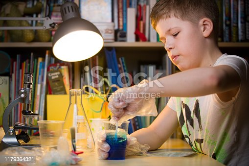 istock A cute elementary school boy is sitting at the table holding a glass with blue liquid. A young scientist makes experiments in his home lab. Indoors. Child and science. 1179364321