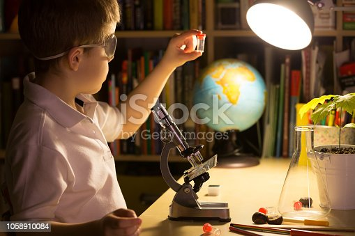 istock Cute elementary school boy looking into microscope at his desk at home. Young scientist making experiments in his home laboratory. Indoors. Child and science. 1058910084