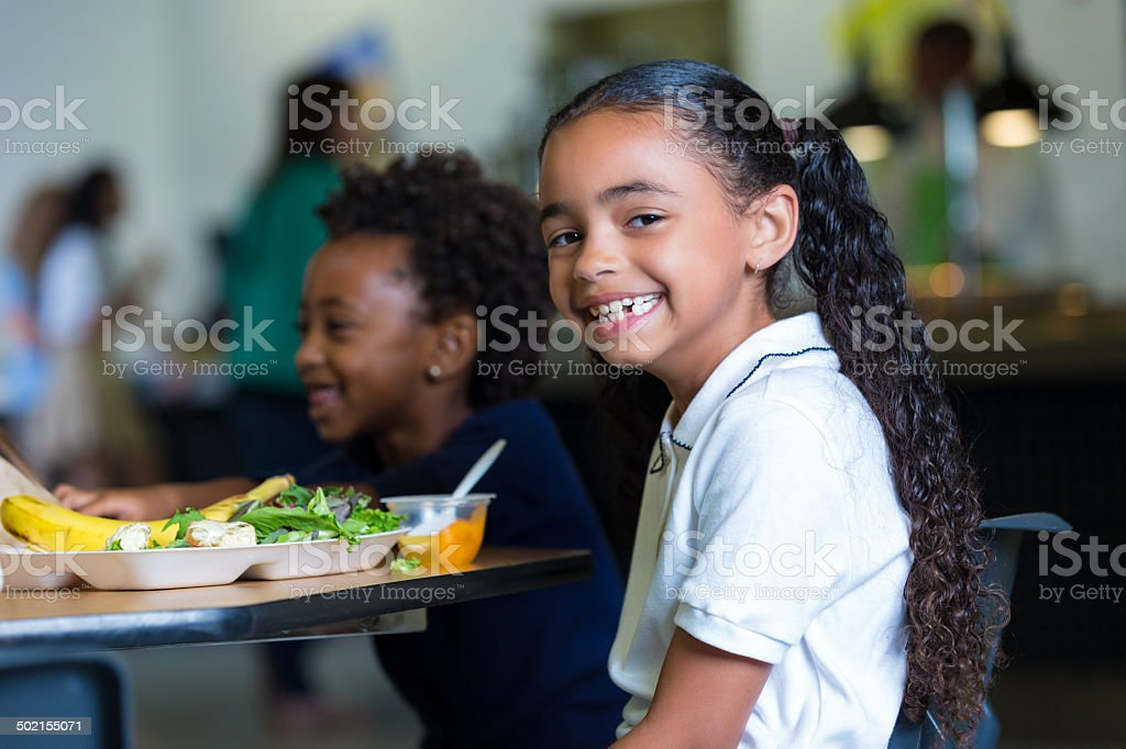 Cute elementary school girl eating healthy lunch in cafeteria stock photo