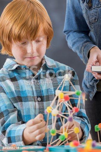 648947070istockphoto Cute elementary school student builds something in engineering club 649355718
