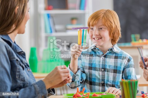 648947070 istock photo Cute elementary schoolboy makes craft in art class 648947016