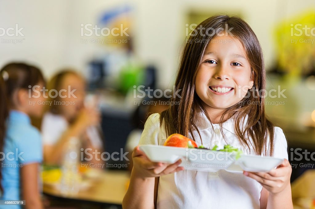 Cute elementary student holding lunch tray in school cafeteria stock photo
