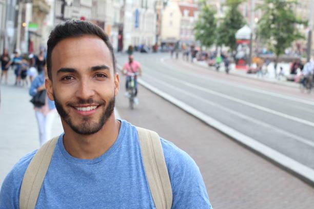 Homem farpado étnico bonito que sorri ao ar livre - foto de acervo
