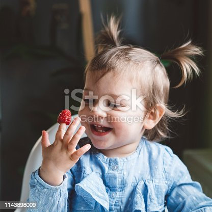 istock Cute excited baby girl with a raspberry on her finger 1143898009