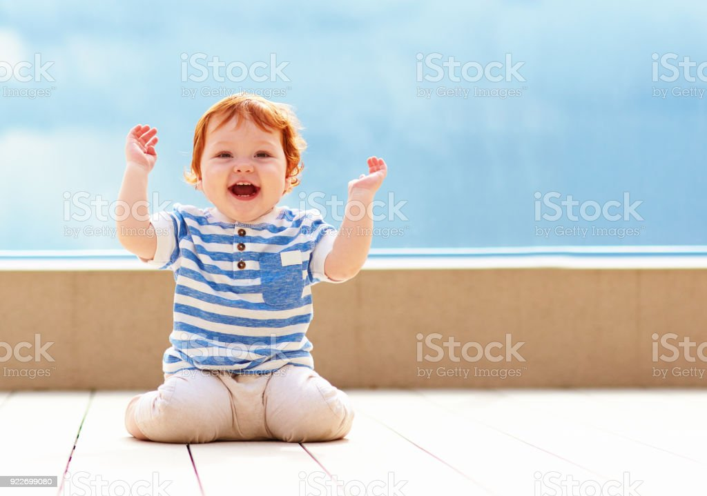 cute excited toddler baby having fun on decking stock photo