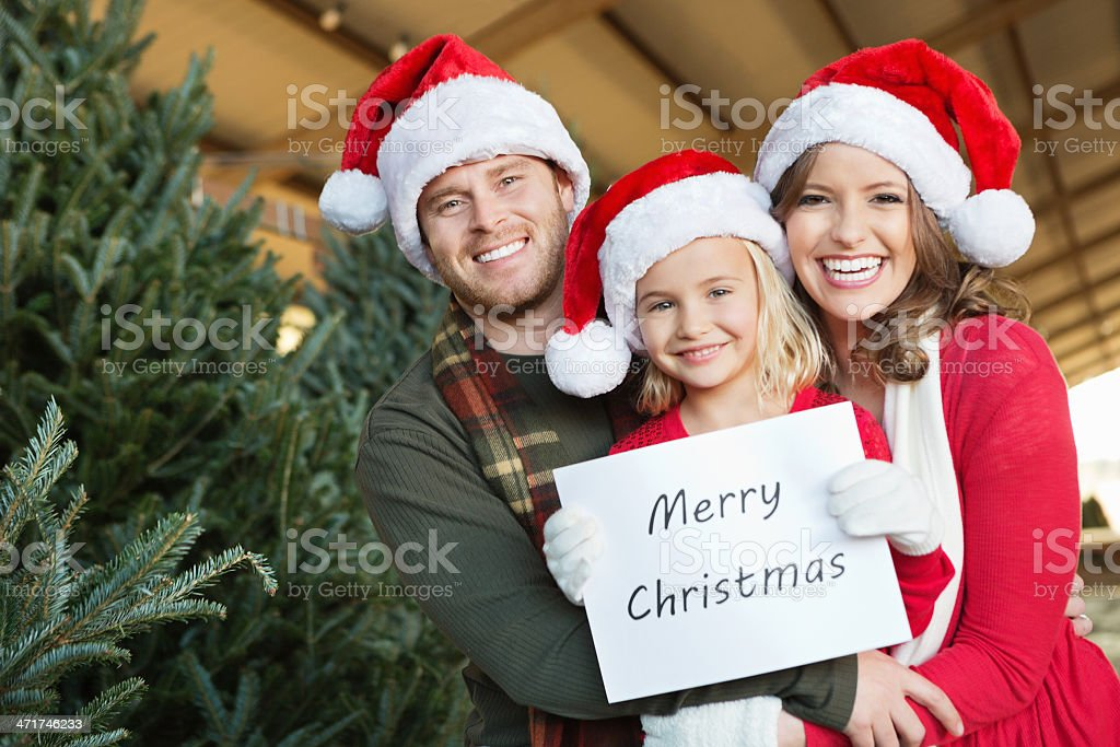 Cute family holding ''Merry Christmas'' sign at tree farm royalty-free stock photo