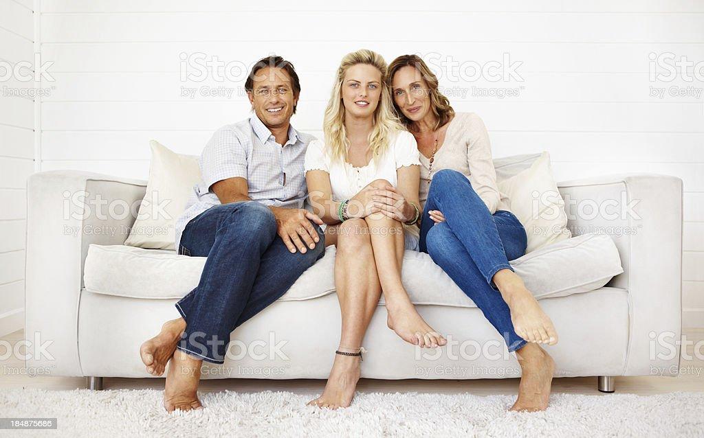 Süße Familie sitzt auf einem sofa zu Hause fühlen – Foto