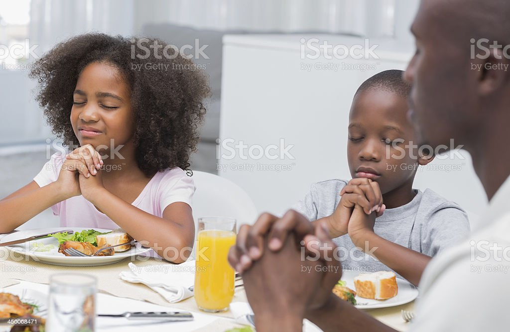 Cute family saying grace before having dinner royalty-free stock photo