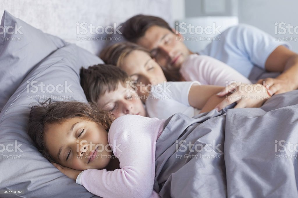 Cute family sleeping in bed stock photo