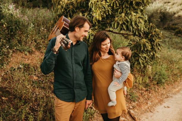 söt familj tar en promenad på landsbygden med sin son vid solnedgången. - happy indie pop bildbanksfoton och bilder