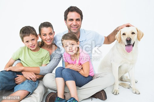 istock Cute family with pet labrador posing and smiling at camera together 691811218