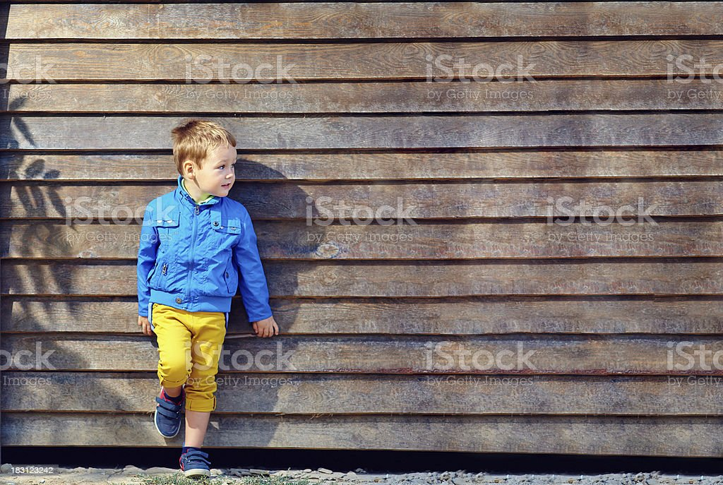 cute fashionable boy in front of wooden wall stock photo