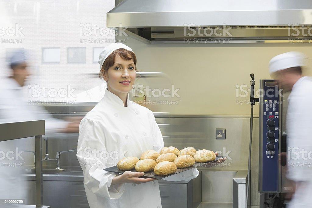 Cute female baker holding a baking tray stock photo