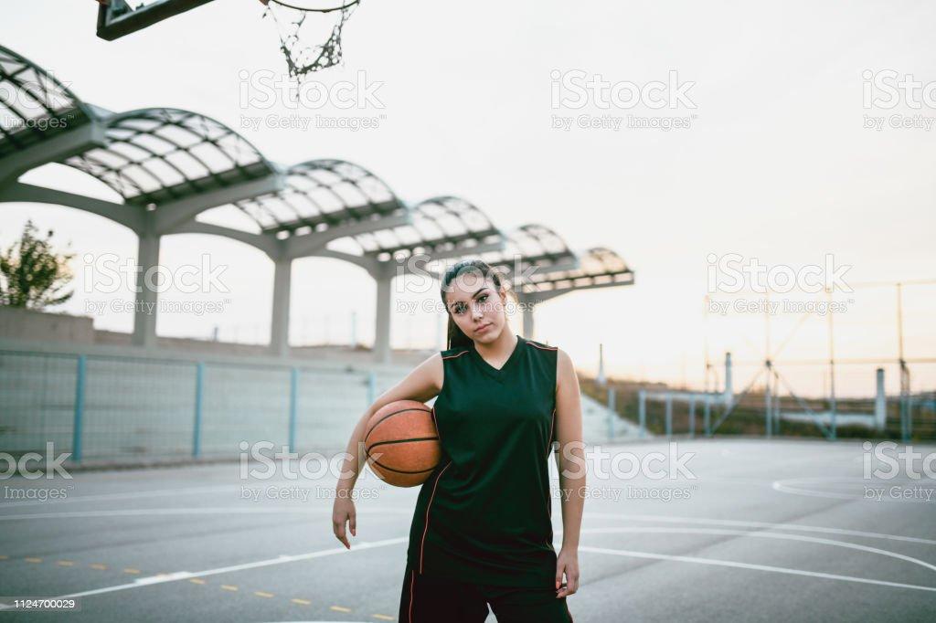 Cute Female Basketball Player Posing Under The Basketball Hoop