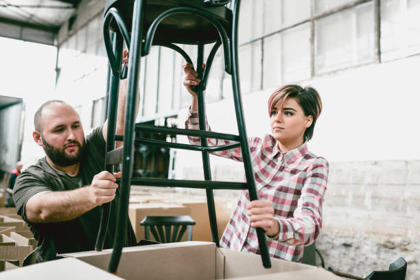 Cute Female Factory Worker Packing a Newly Made Chairs Cute Female Factory Worker Packing a Newly Made Chairs distribution center stock pictures, royalty-free photos & images