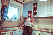 Cute Female in Kitchen Drinking Coffee and Using Smartphone