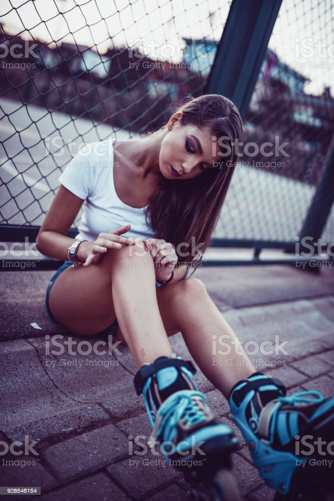 Cute Female In Pain Applying Bandage on Bloody Knee stock photo
