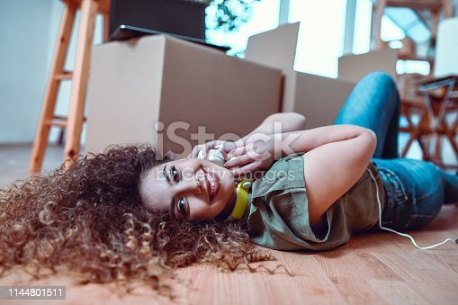 Cute Female Listening To Music While Lying Down On Floor