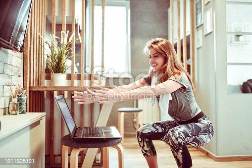Cute Female Practicing Squats In Kitchen