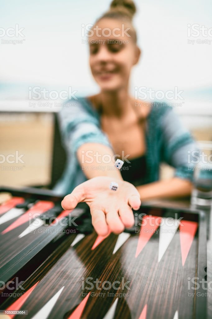 Cute Female Rolling Dices stock photo